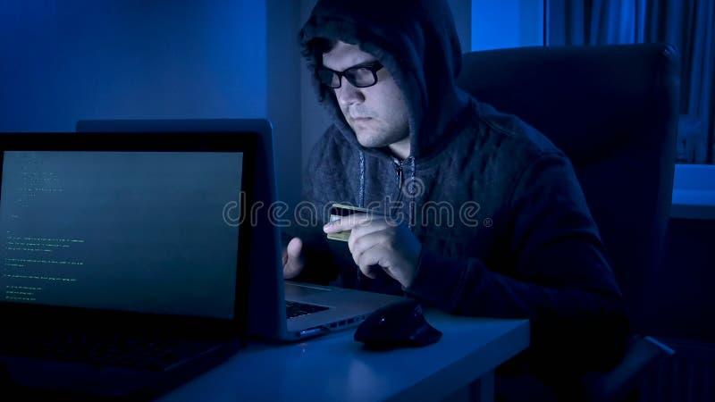 Jeune pirate informatique masculin dans le capot travaillant sur l'ordinateur portable pour voler l'argent de la carte de crédit photographie stock libre de droits