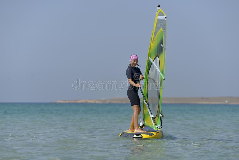 Jeune planche à voile de femme de sports en mer un jour ensoleillé photos libres de droits