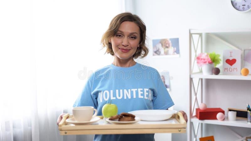 Jeune plateau de sourire de participation de volontaire avec la nourriture de petit d?jeuner dans des mains, gentillesse photo libre de droits