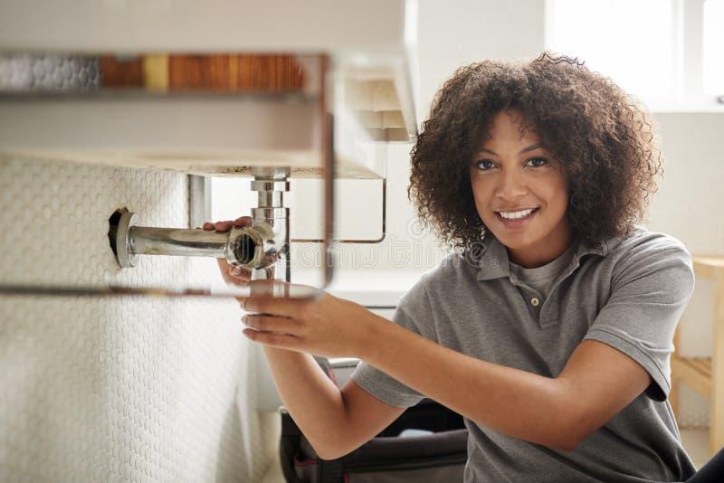 Jeune plombier féminin noir s'asseyant sur le plancher fixant un évier de salle de bains, regardant à la caméra images libres de droits
