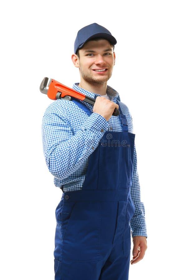 Jeune plombier jugeant la clé à tube d'isolement photographie stock