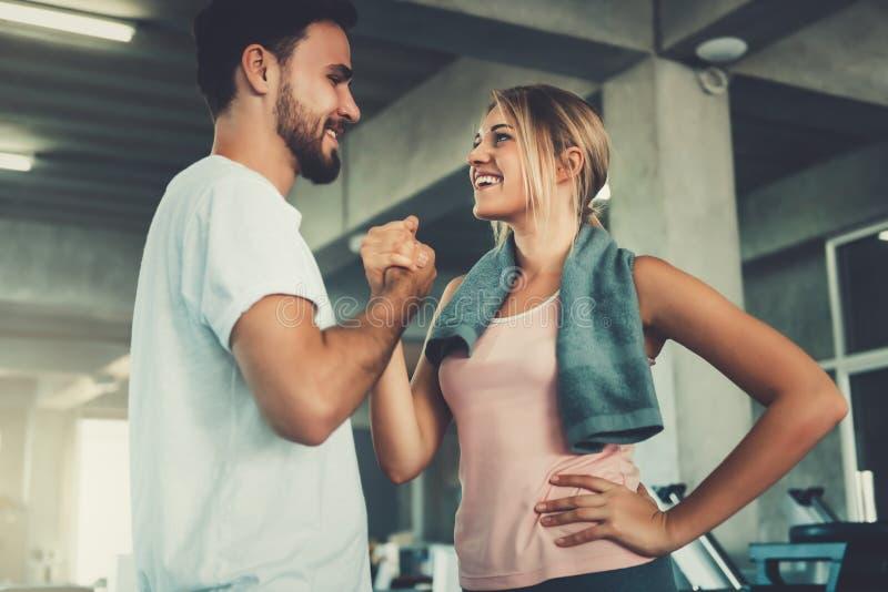 Jeune poignée de main attrayante de couples après séance d'entraînement dans le gymnase de forme physique , Le portrait de l'homm photo libre de droits