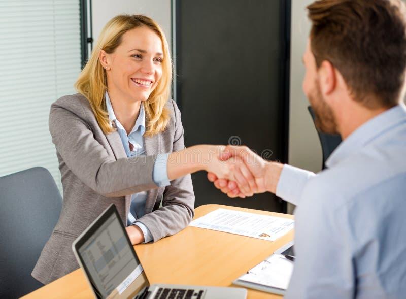 Jeune poignée de main attrayante de femme à la fin d'une entrevue d'emploi photos stock