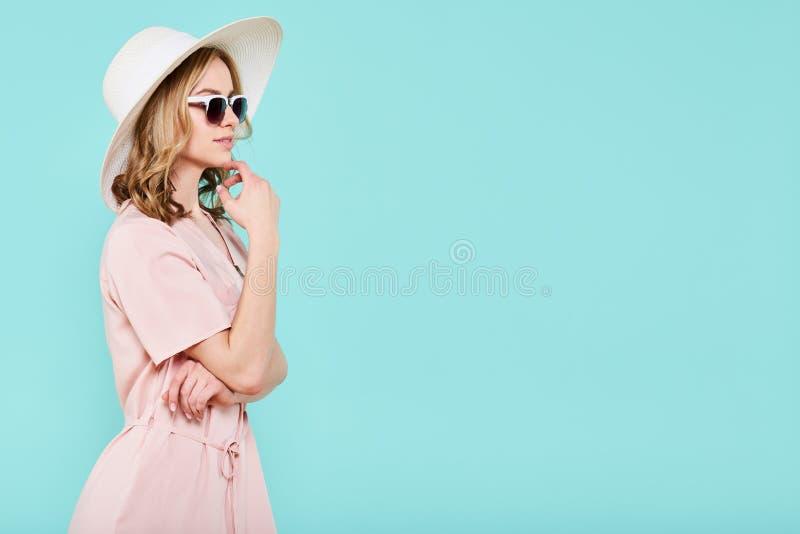Jeune port attrayant élégant de femme pâle - robe, chapeau de paille rose et lunettes de soleil d'été, pensant à ses vacances d'é photo stock