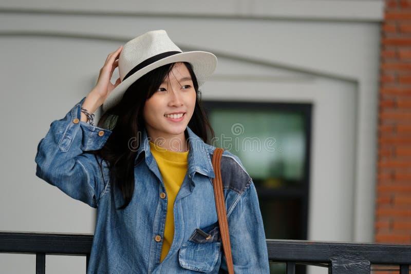Jeune portrait asiatique de femme souriant avec bonheur au fond d'extérieur de ville, lifesyle occasionnel, blogger de voyage photographie stock libre de droits