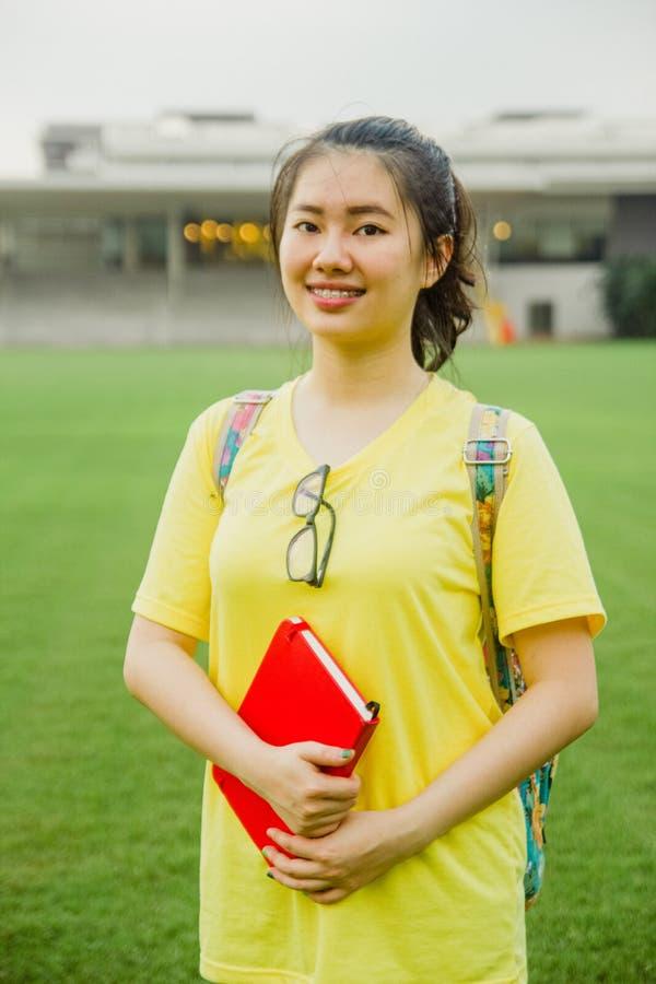 Jeune portrait d'étudiante souriant avec un livre sur le champ d'herbe pendant l'après-midi dans le campus image stock