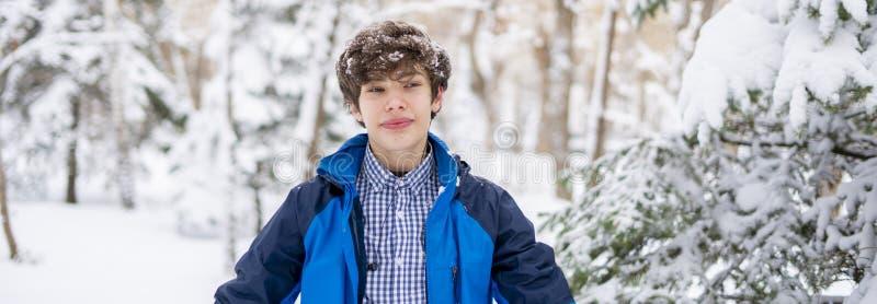 Jeune portrait de l'adolescent masculin marchant dans la forêt neigeuse f d'hiver photographie stock libre de droits