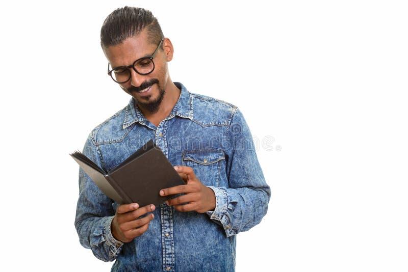 Jeune portrait indien heureux de studio de livre de lecture d'homme sur le fond blanc photo stock
