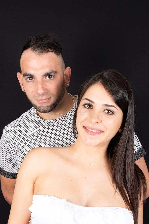 Jeune portrait romantique d'étreinte de couples à l'arrière-plan noir dans l'amour photos stock