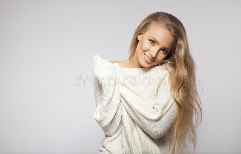 Jeune pose blonde renversante sur le fond gris photographie stock