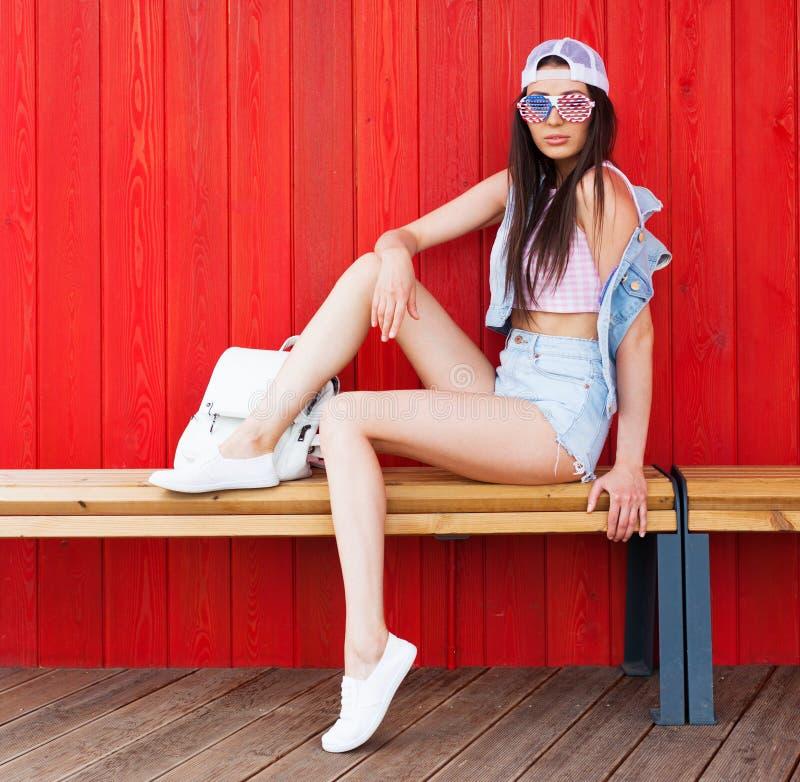 Jeune pose bronzage de sourire heureuse de femme de brune extérieure dans le dessus rose de port de vintage d'heure d'été, les sh image libre de droits