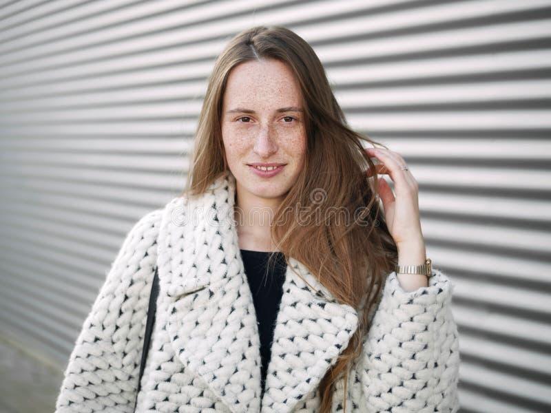 Jeune pose caucasienne sérieuse habillée à la mode de femme extérieure la saison froide de fond géométrique brouillée par ville u photos libres de droits