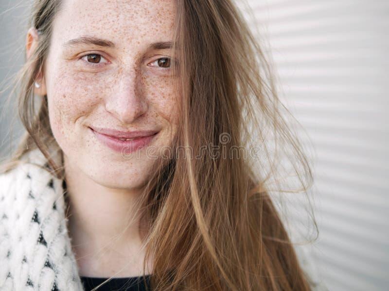 Jeune pose caucasienne sérieuse habillée à la mode de femme extérieure la saison froide de fond géométrique brouillée par ville u photographie stock libre de droits