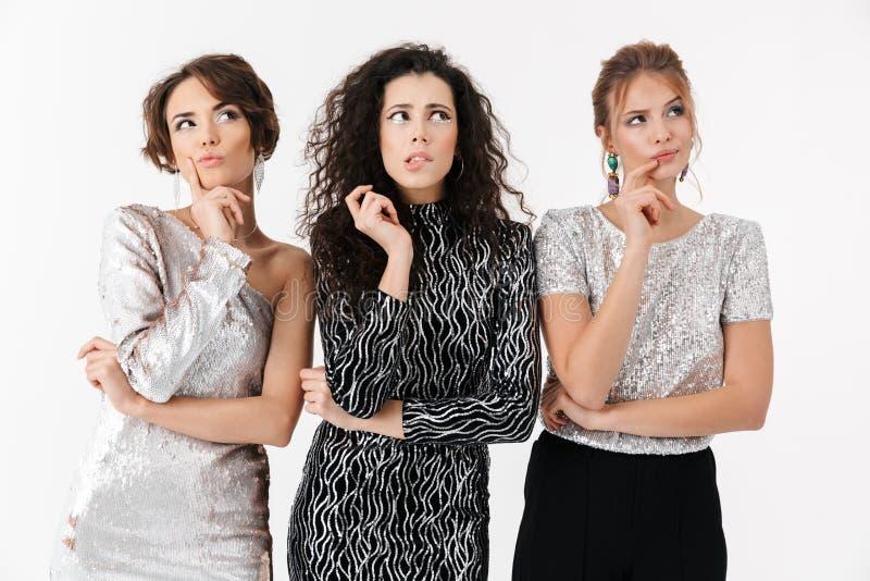 Jeune pose de pensée d'amies de femmes d'isolement au-dessus du fond blanc de mur sur une partie photo stock