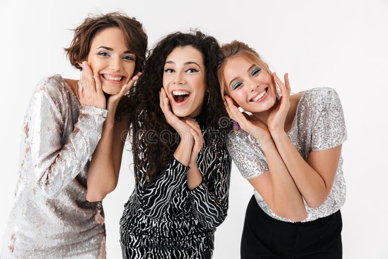 Jeune pose heureuse d'amies de femmes d'isolement au-dessus du fond blanc de mur Sur une r?ception images stock