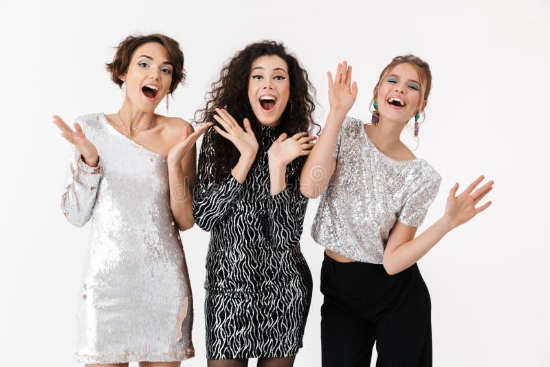 Jeune pose heureuse d'amies de femmes d'isolement au-dessus du fond blanc de mur Sur une r?ception photo libre de droits