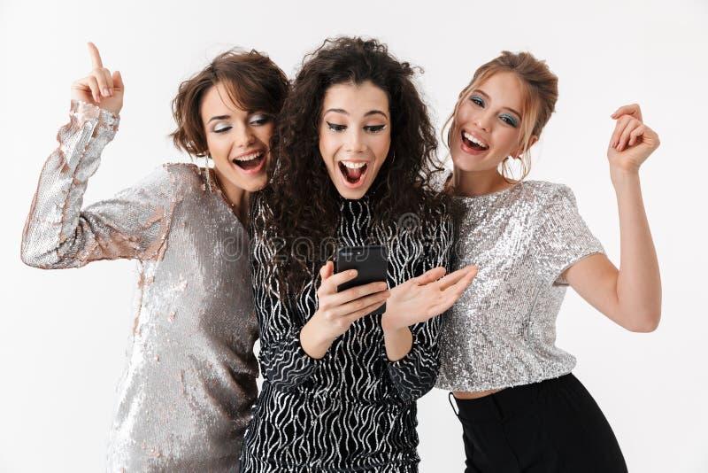 Jeune pose heureuse d'amies de femmes d'isolement au-dessus du fond blanc de mur Sur une r photographie stock libre de droits