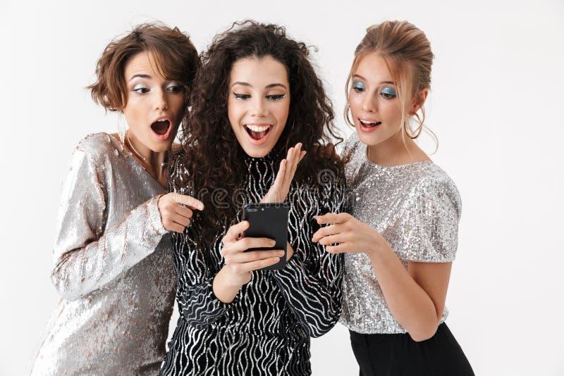 Jeune pose heureuse d'amies de femmes d'isolement au-dessus du fond blanc de mur Sur une r images libres de droits