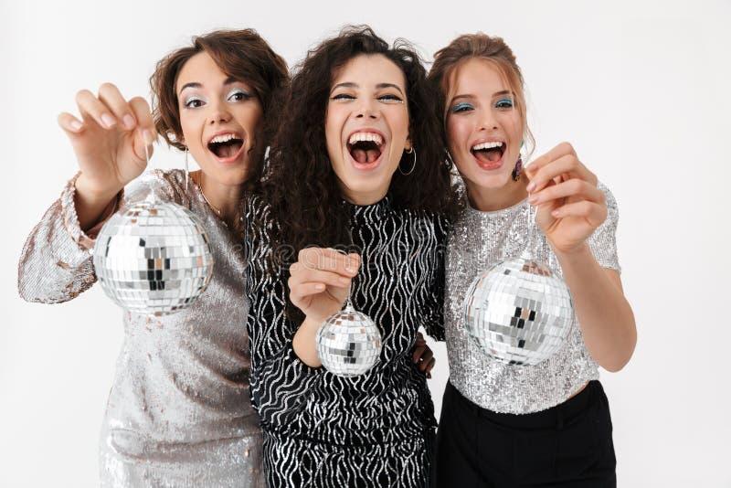 Jeune pose heureuse d'amies de femmes d'isolement au-dessus du fond blanc de mur Sur une r photographie stock