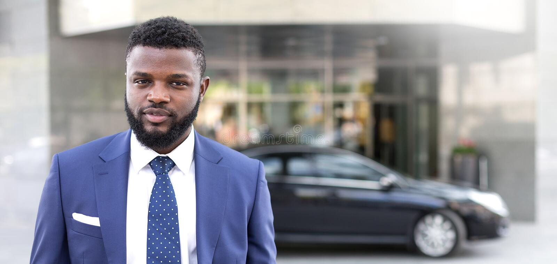 Jeune position africaine d'homme d'affaires près de l'immeuble de bureaux et regarder la caméra photos stock