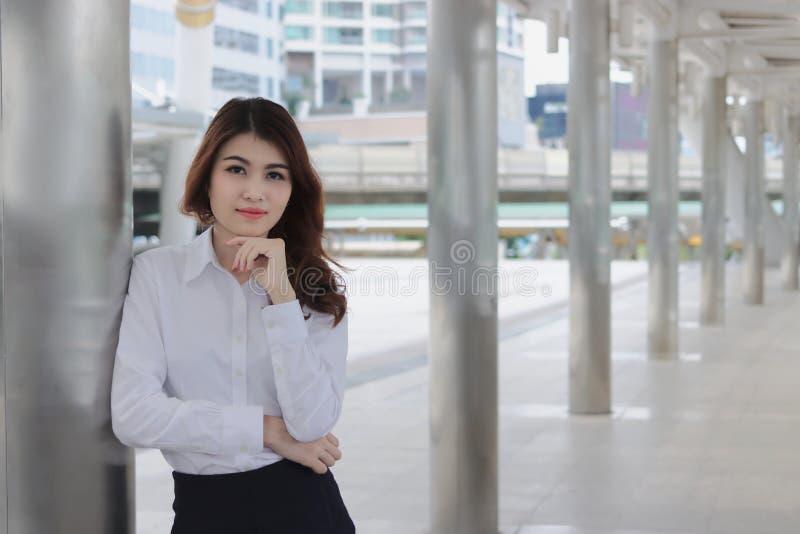 Jeune position asiatique de femme d'affaires de direction et regarder à la caméra le passage couvert du bureau extérieur photographie stock libre de droits