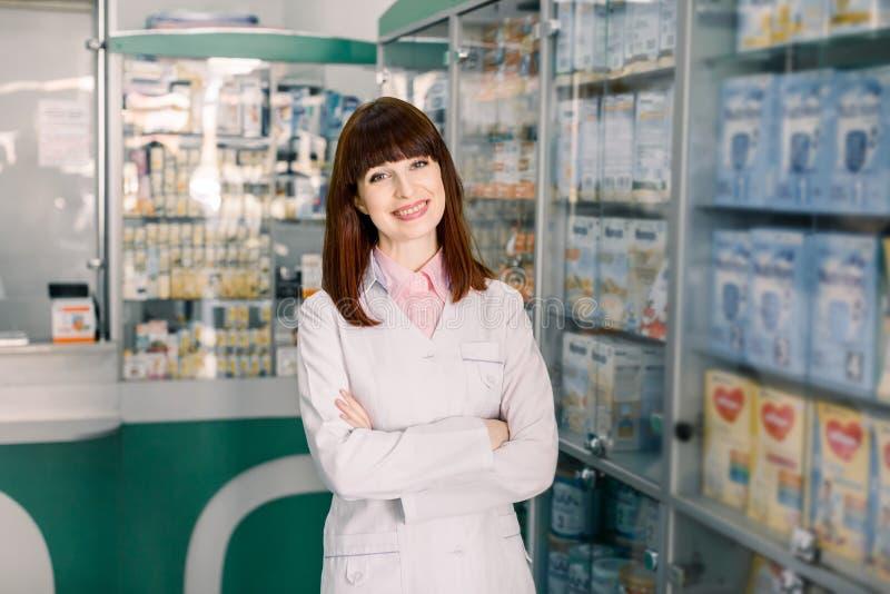 Jeune position caucasienne de sourire gaie de femme de chimiste de pharmacien dans la pharmacie de pharmacie photographie stock