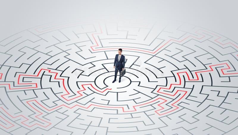 Jeune position d'entrepreneur ? un milieu d'un labyrinthe photo stock