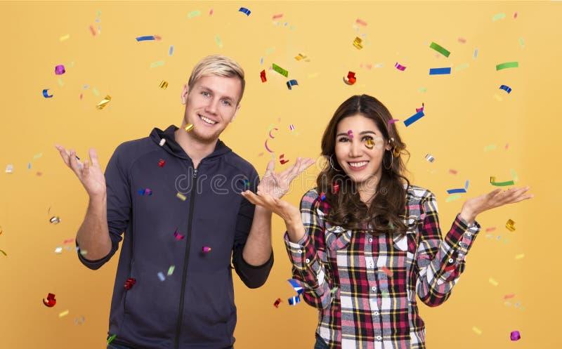 Jeune position de couples debout sous la pluie de confettis photo libre de droits