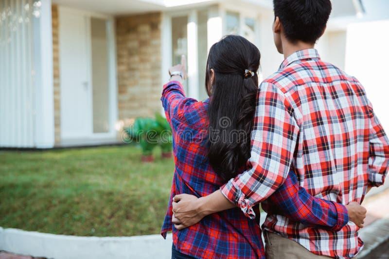 Jeune position de couples devant leur nouvelle maison photo libre de droits