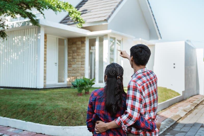 Jeune position de couples devant leur nouvelle maison photographie stock