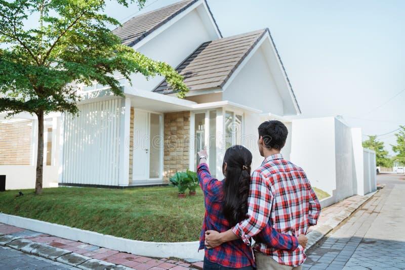 Jeune position de couples devant leur nouvelle maison photos libres de droits