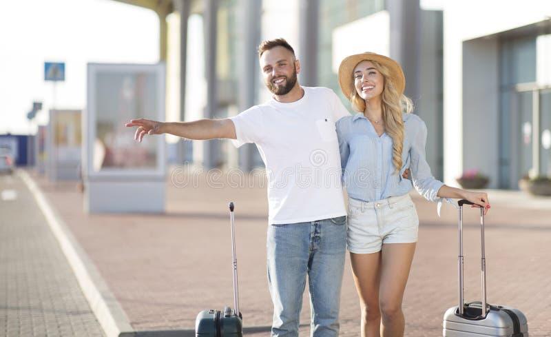 Jeune position de couples près de l'aéroport essayant d'arrêter la voiture photographie stock