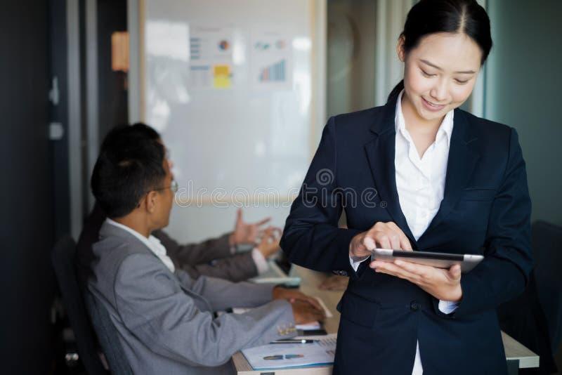 Jeune position de femme d'affaires avec le comprimé près de la fenêtre de bureau, concept d'affaires photo libre de droits