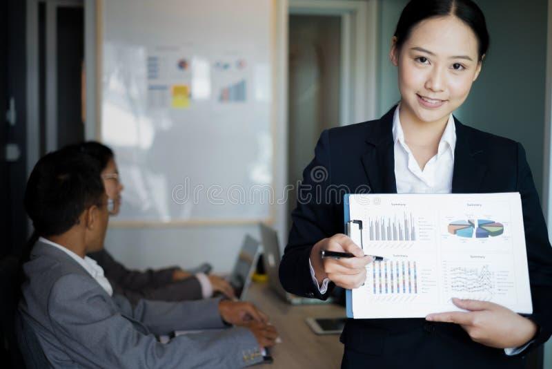 Jeune position de femme d'affaires avec le document près de la fenêtre de bureau, concept d'affaires photo stock