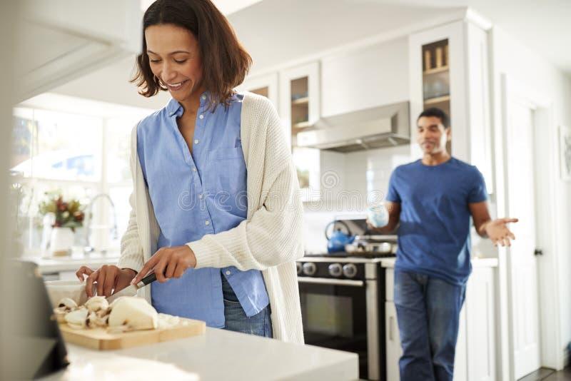 Jeune position de femme d'Afro-américain dans la cuisine préparant la nourriture, sa position d'associé derrière parler, foyer su images stock