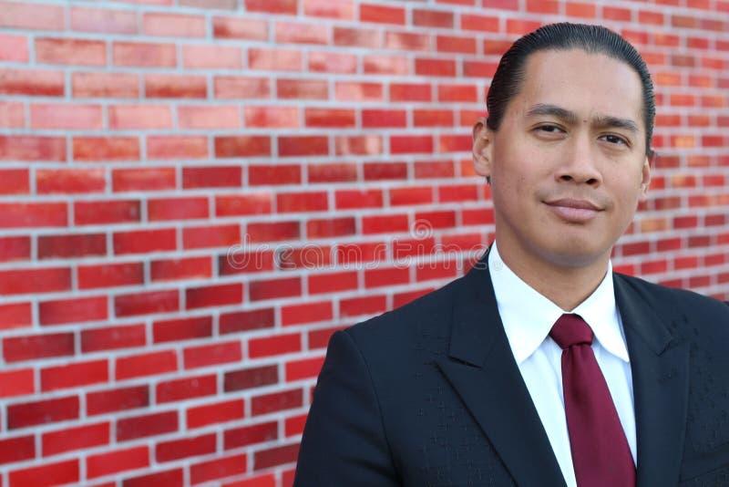 Jeune position de sourire asiatique d'homme d'affaires d'intérieur avec l'espace de copie du côté gauche de la photo photo stock
