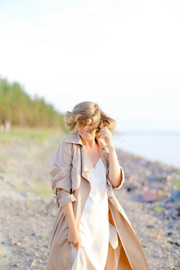 Jeune position de sourire de femme sur la plage de mer et le manteau de port avec la robe blanche photographie stock libre de droits
