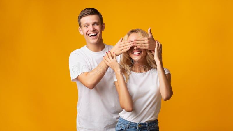 Jeune position de type derrière l'amie et fermeture de ses yeux photographie stock