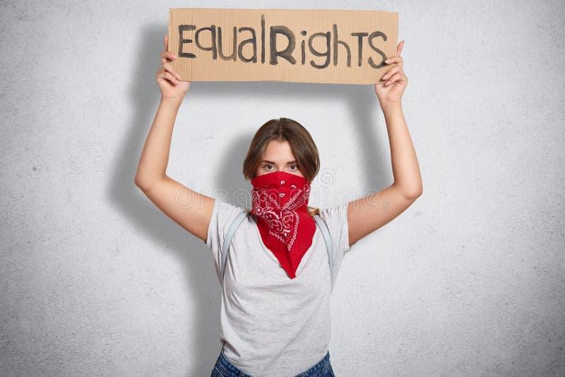 Jeune position féministe sûre indépendante au-dessus de fond gris dans le studio, soulevant ses mains, tenant l'égal de signe image stock