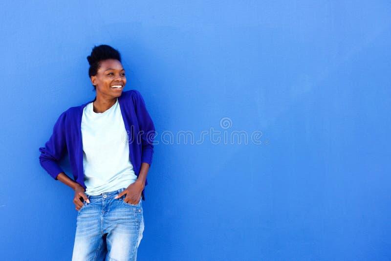 Jeune position femelle africaine heureuse contre le mur bleu photographie stock