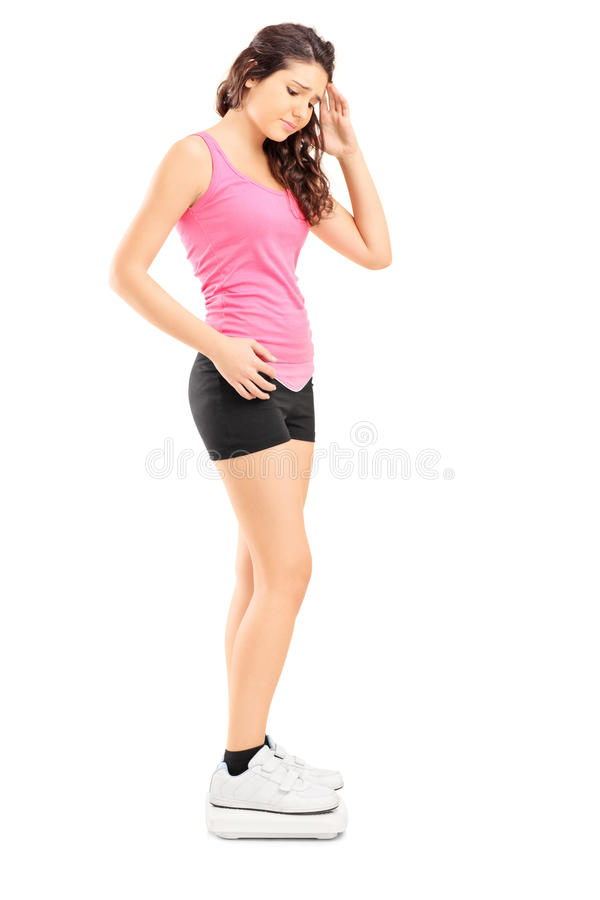 Jeune position femelle déçue sur l'échelle de poids photo stock