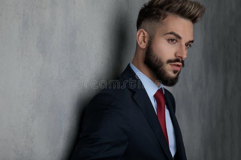 Jeune position fraîche d'homme d'affaires contre le mur gris de studio photo stock