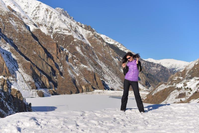 Jeune position heureuse de femme souriant en montagnes neigeuses image libre de droits