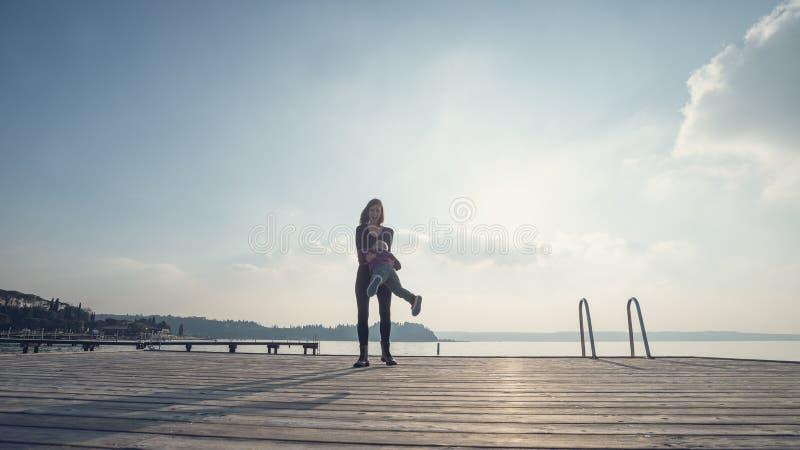 Jeune position heureuse de mère sur le pilier en bois tournant son fils photos stock