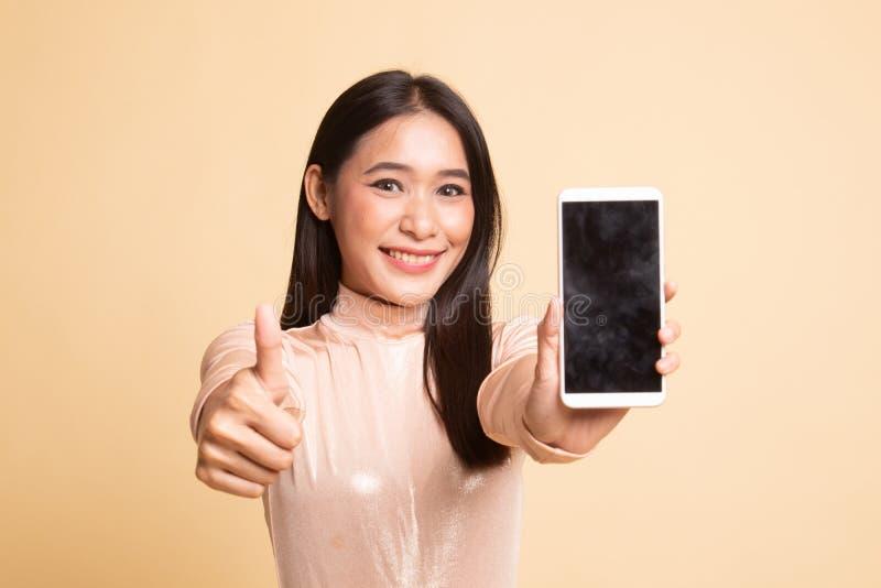Jeune pouce asiatique d'exposition de femme avec le t?l?phone portable photo libre de droits
