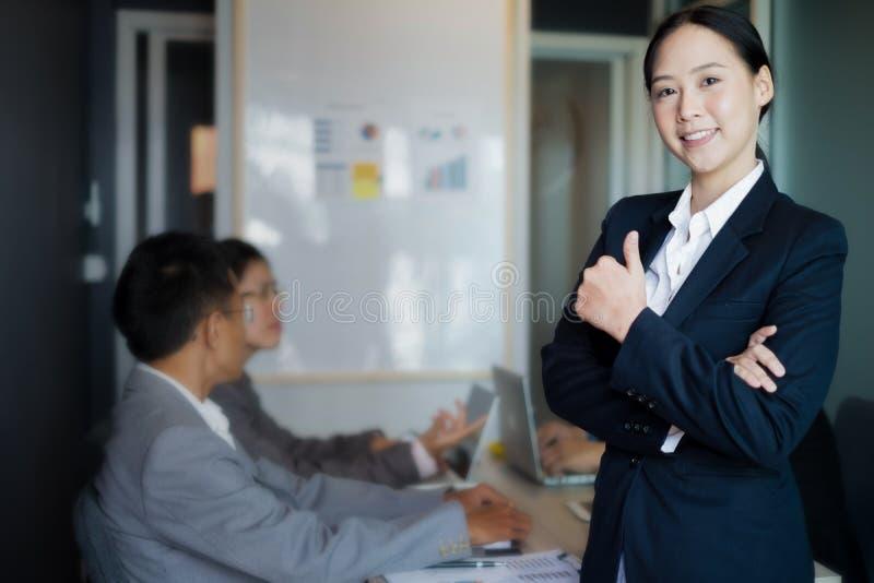 Jeune pouce de position de femme d'affaires avec le comprimé près de la fenêtre de bureau, concept d'affaires photos stock