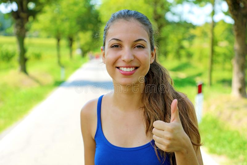 Jeune pouce heureux d'apparence de femme de forme physique vers le haut d'extérieur image libre de droits