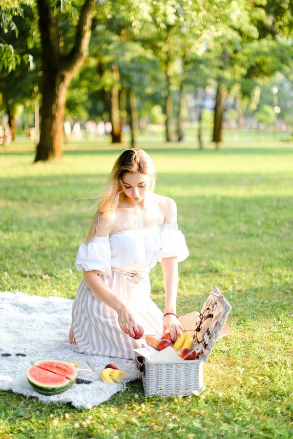 Jeune préparation blonde de fille forpicnic en parc, se reposant sur le plaid près de la boîte et du waterlemon photographie stock