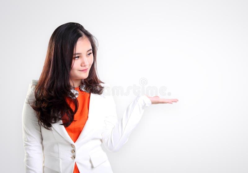 Jeune présentation professionnelle femelle sur le blanc photo stock