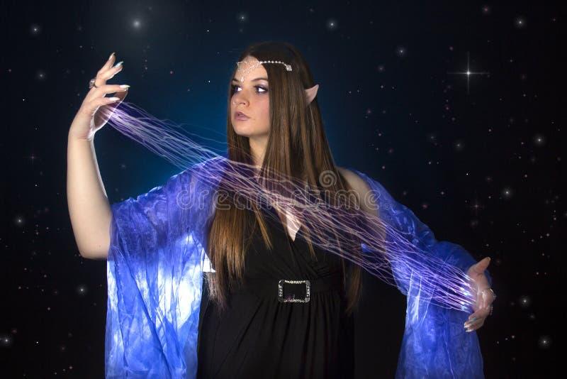 Jeune princesse féminine d'elfe jouant avec la magie la nuit photo libre de droits